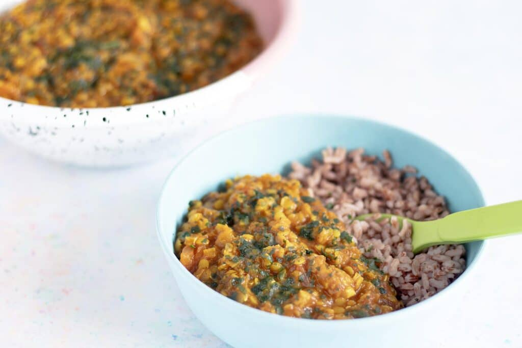 dal and rice in bowl with green spoon and bowl of dal in background