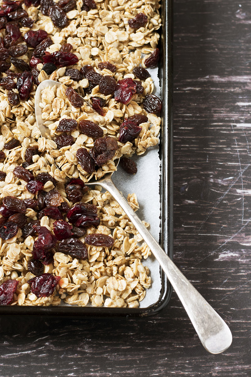 vertical image of granola on baking tray with serving spoon