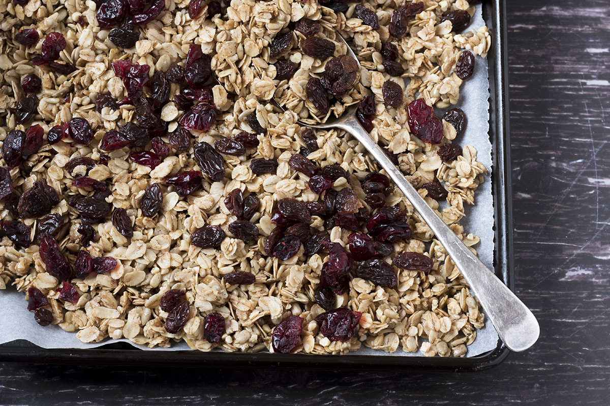 healthy homemade granola on tray with silver spoon