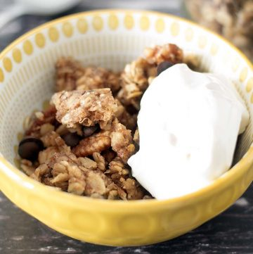 vegan banana granola with chocolate chips in yellow bowl with yoghurt