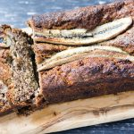banana bread on wooden board with two slices cut