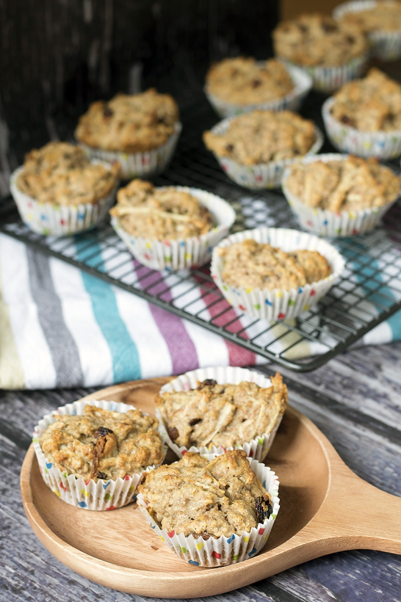wholemeal healthy muffins on wooden plate with cooling rack in background