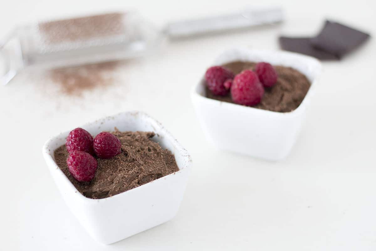 chocolate avocado mousse with grated chocolate and raspberries in white dish. By Sneaky veg