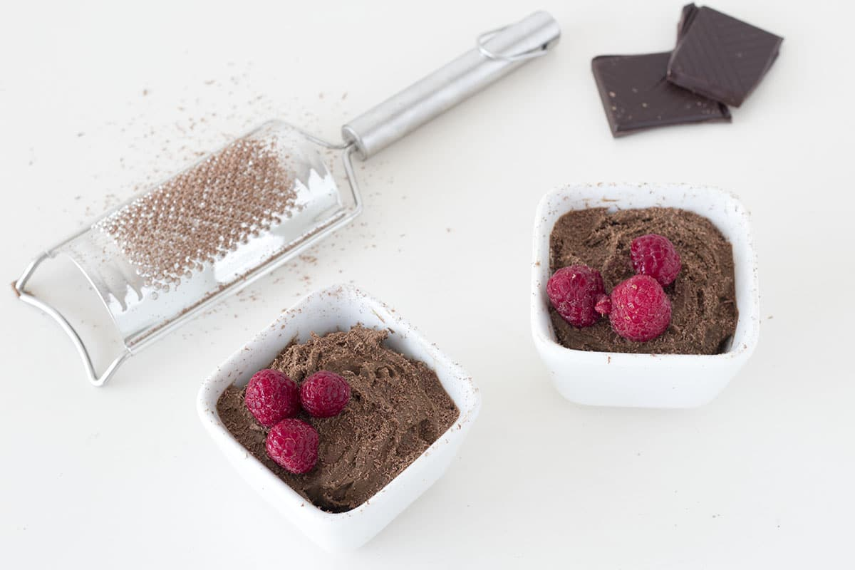 vegan chocolate avocado mousse with grated chocolate and raspberries in white dish. By Sneaky veg