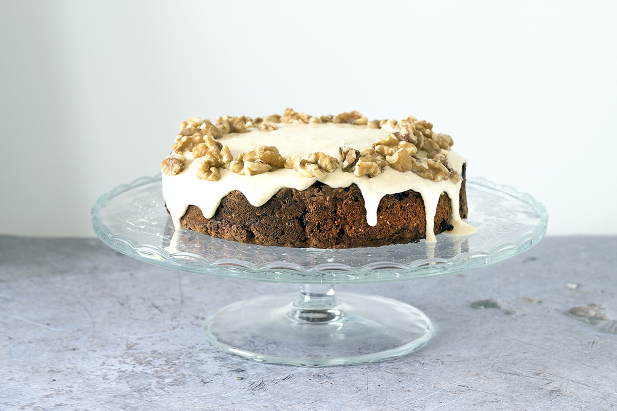 Date, carrot and banana cake on glass cake stand. Recipe by Sneaky Veg