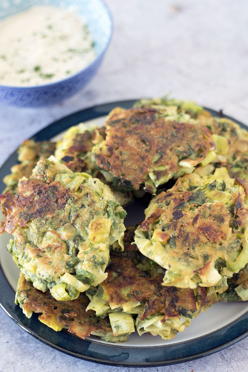 Vegan leek fritters on plate with tahini sauce in background