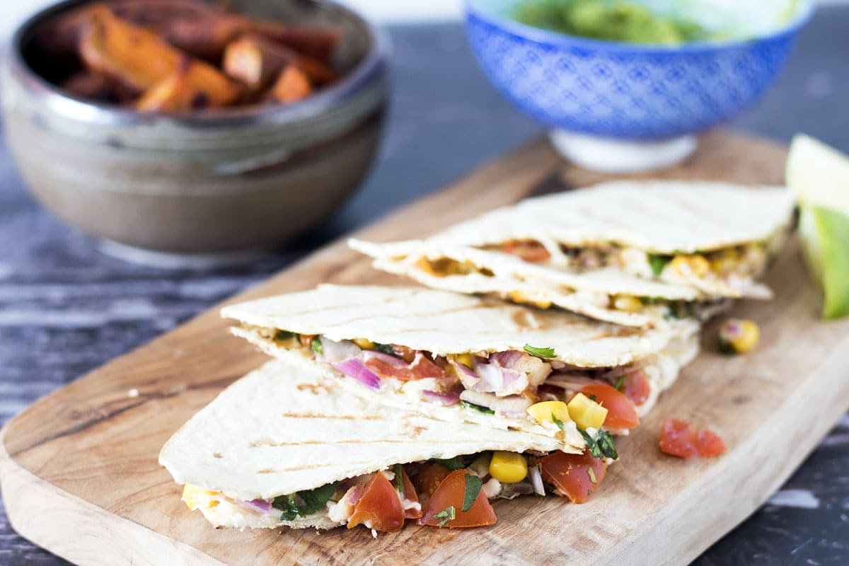 cut quesadilla on wooden board with sides in background