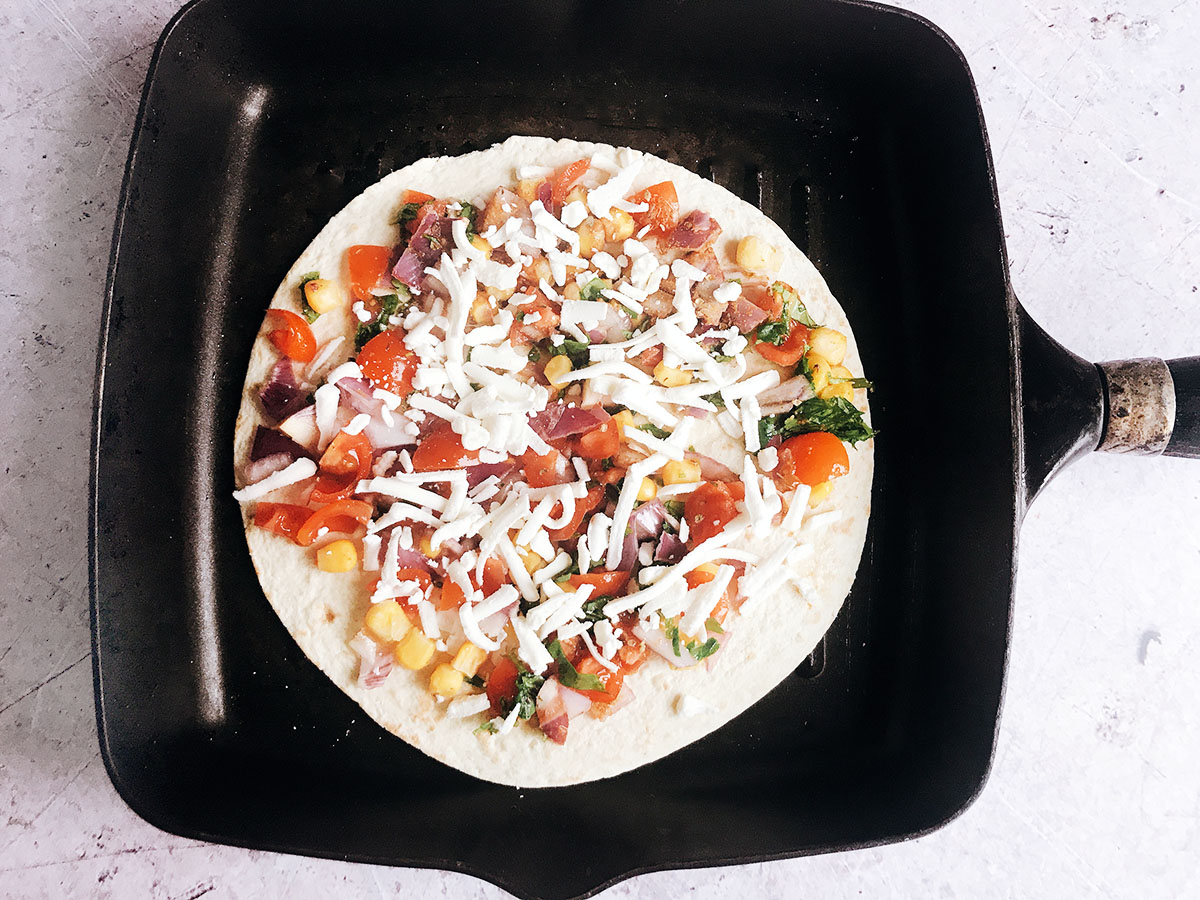 cooking a quesadilla - tortilla on pan with fillings and cheese