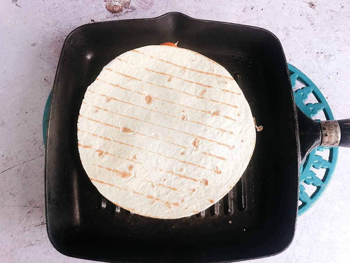quesadilla cooking on griddle pan