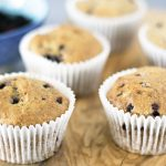 wholewheat blackberry muffins on wooden board with blackberries in blue bowl