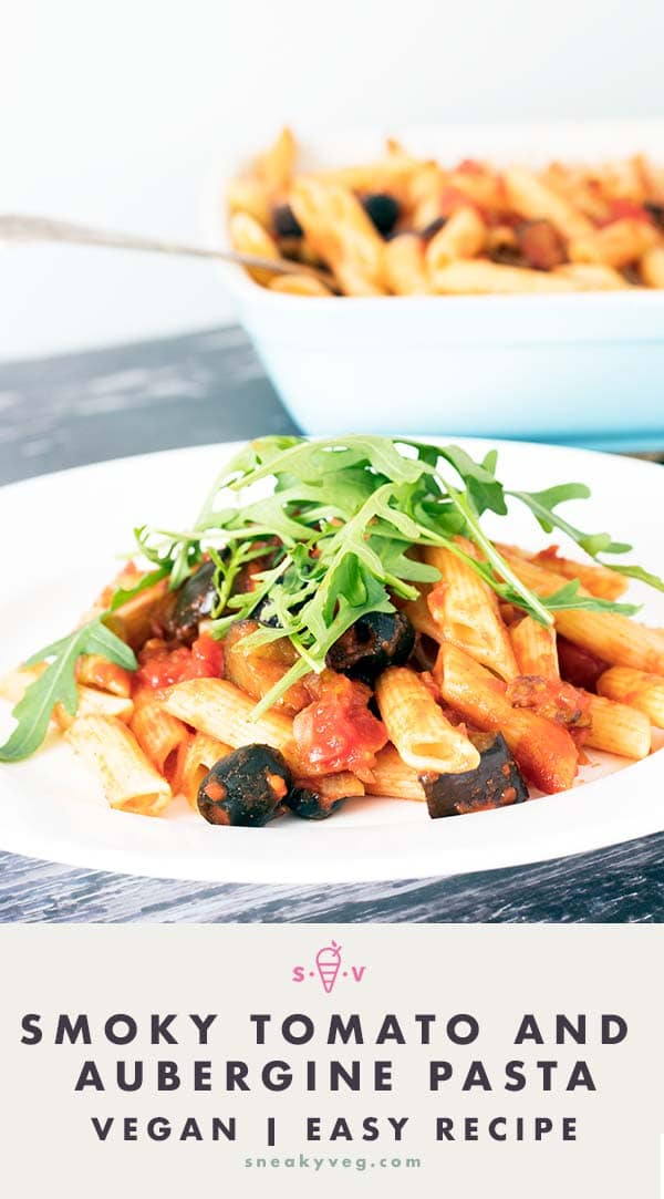 pasta with smoked paprika sauce, tomatoes and aubergines on white plate. Rocket on top.