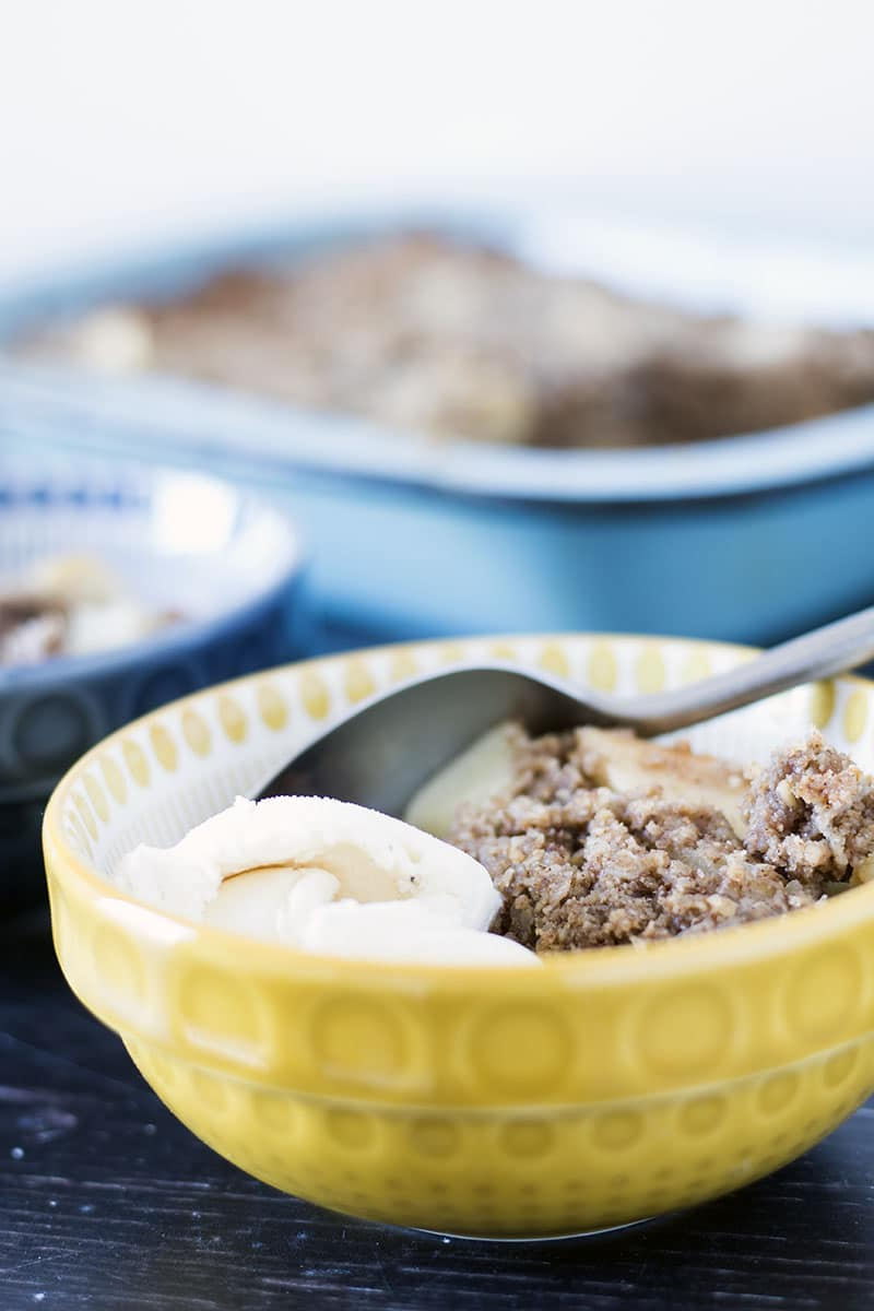 healthy apple crumble in yellow and blue bowls