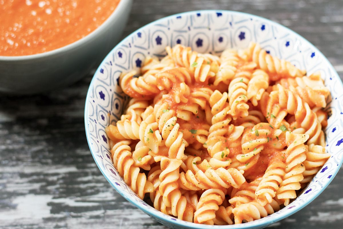 red pasta sauce in bowl with extra sauce in bowl behind