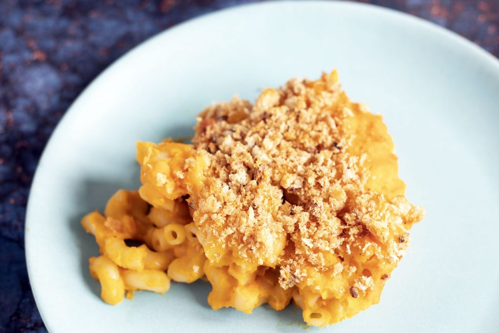 portion of butternut squash macaroni cheese on a blue plate