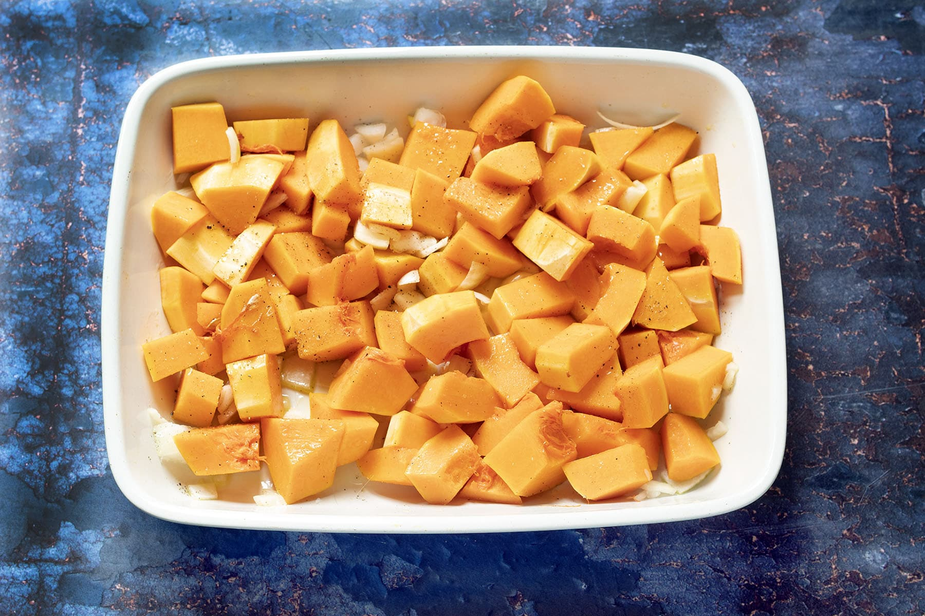 uncooked butternut squash and onion in roasting dish