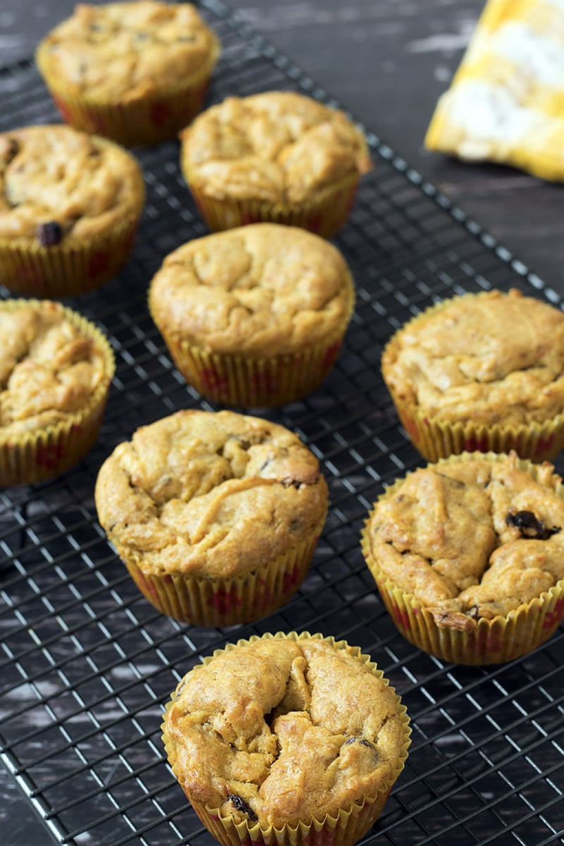 carrot and banana muffins on cooling rack with yellow cloth in background