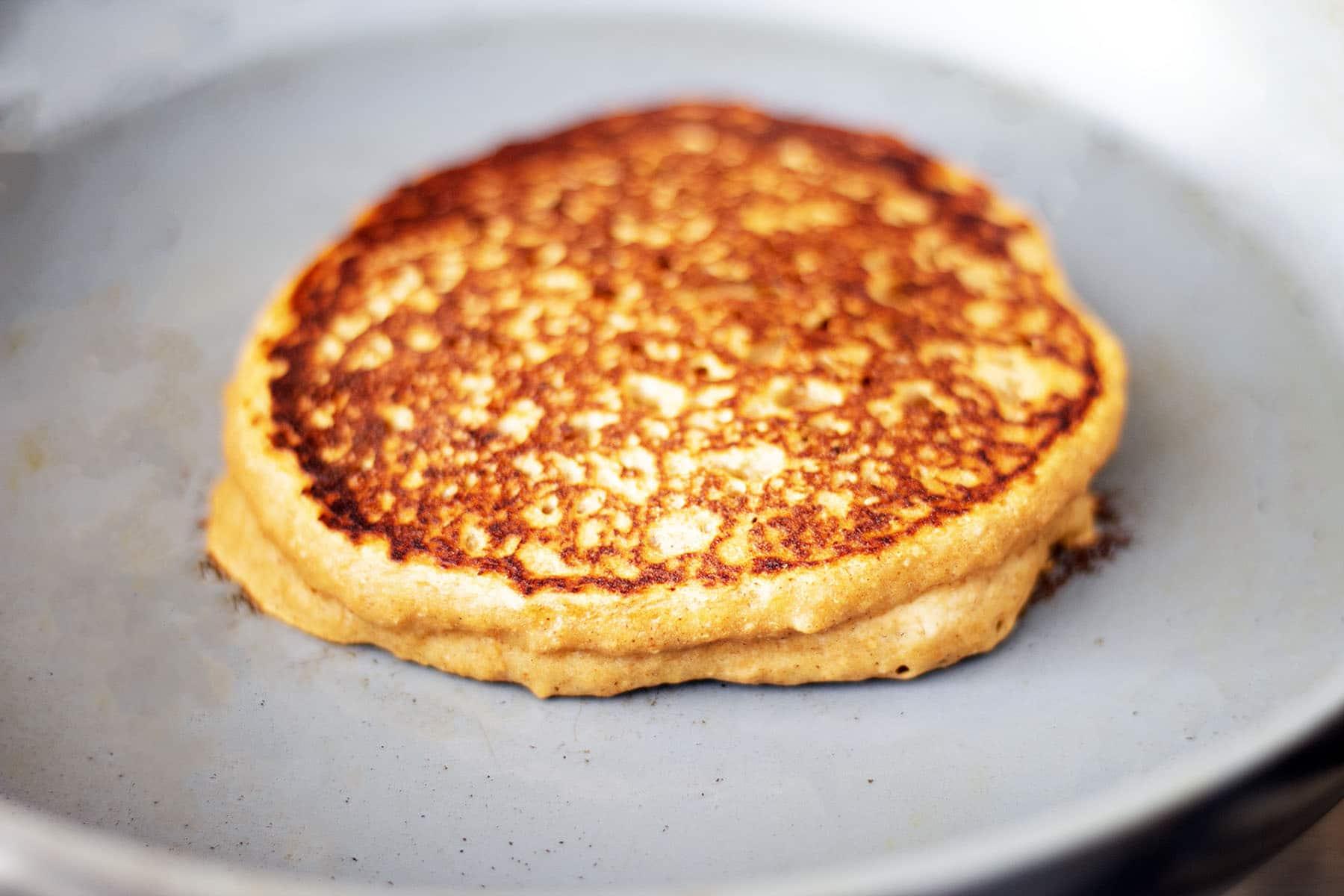 sweet potato pancake cooking on grey pan