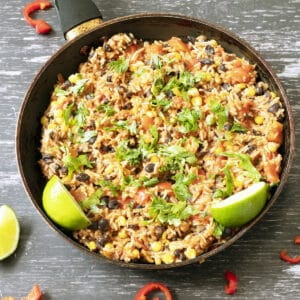 mexican rice with limes and coriander in pan
