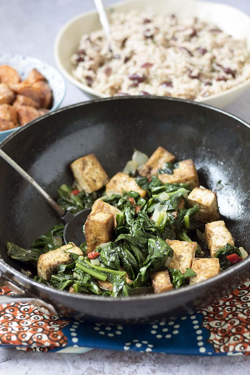 jerk tofu and callaloo or spinach with rice and beans and sweet potatoes in background