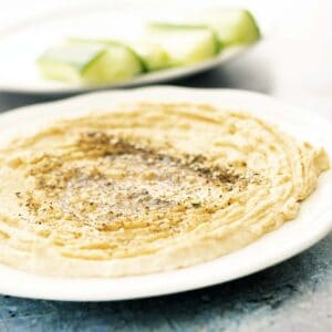 hummus on white plate with cucumber in background