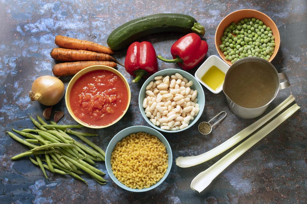 ingredients for minestrone soup on blue background