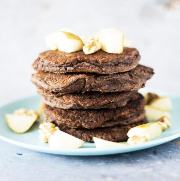 stack of pear, chocolate and coconut flour pancakes on blue plate