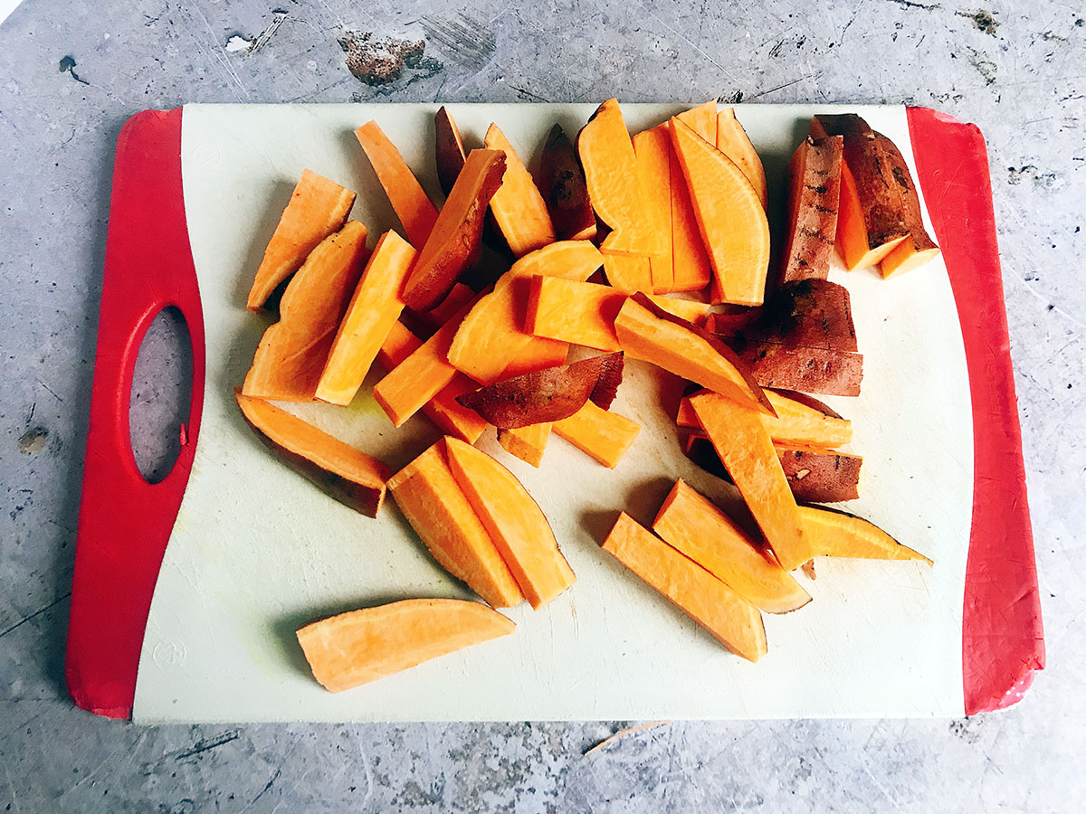 uncooked sweet potato wedges on board
