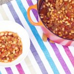 smoky baked beans with aubergine in pan and white bowl on striped background