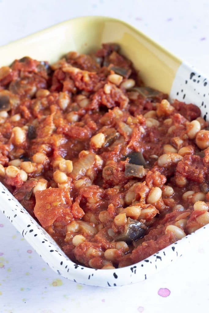 homemade smoky baked beans in yellow and white dish