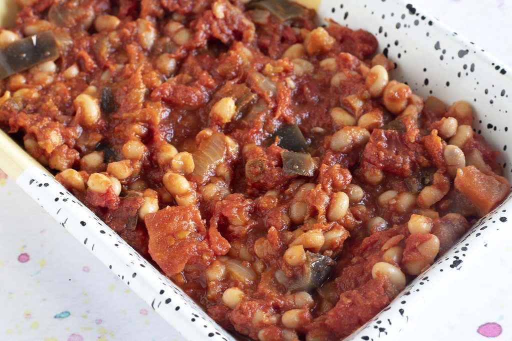homemade smoky baked beans with aubergine in oven dish