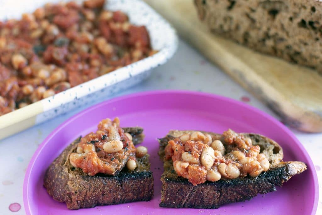 beans on toast on pink plate with beans and bread in background