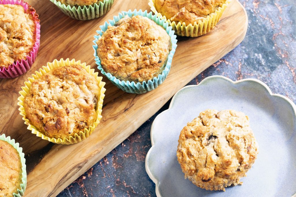 banana and almond muffins in colourful cases with one muffin on blue plate