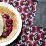 cinnamon wraps on plate with berry compote and nice cream