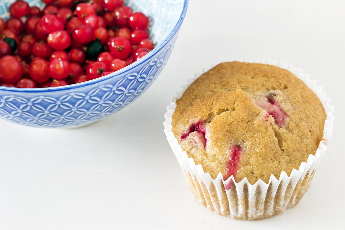 close up of a redcurrant muffin and blue bowl with redcurrants