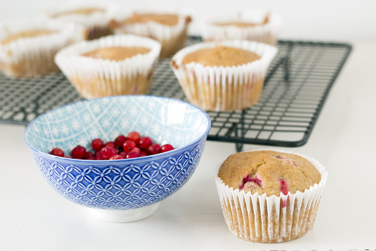 redcurrant muffins on table and cooling rack with bowl of redcurrants in foreground