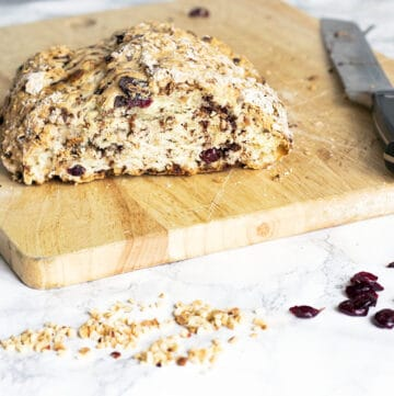 chocolate chip soda bread with hazelnuts and cranberries on wooden board