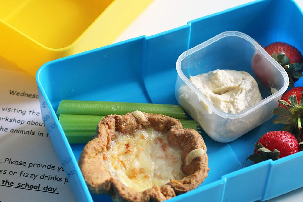 lunchbox with mini baked bean and cheese pies, celery, strawberries and hummus
