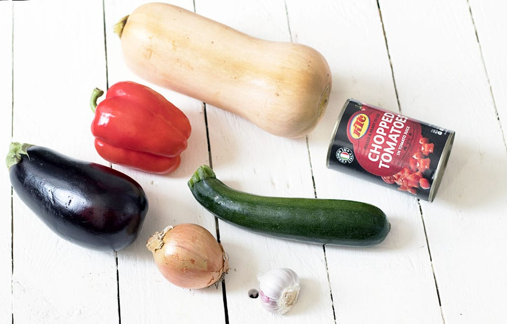 aubergine, pepper, courgette, onion, garlic, squash and tinned tomatoes on white background
