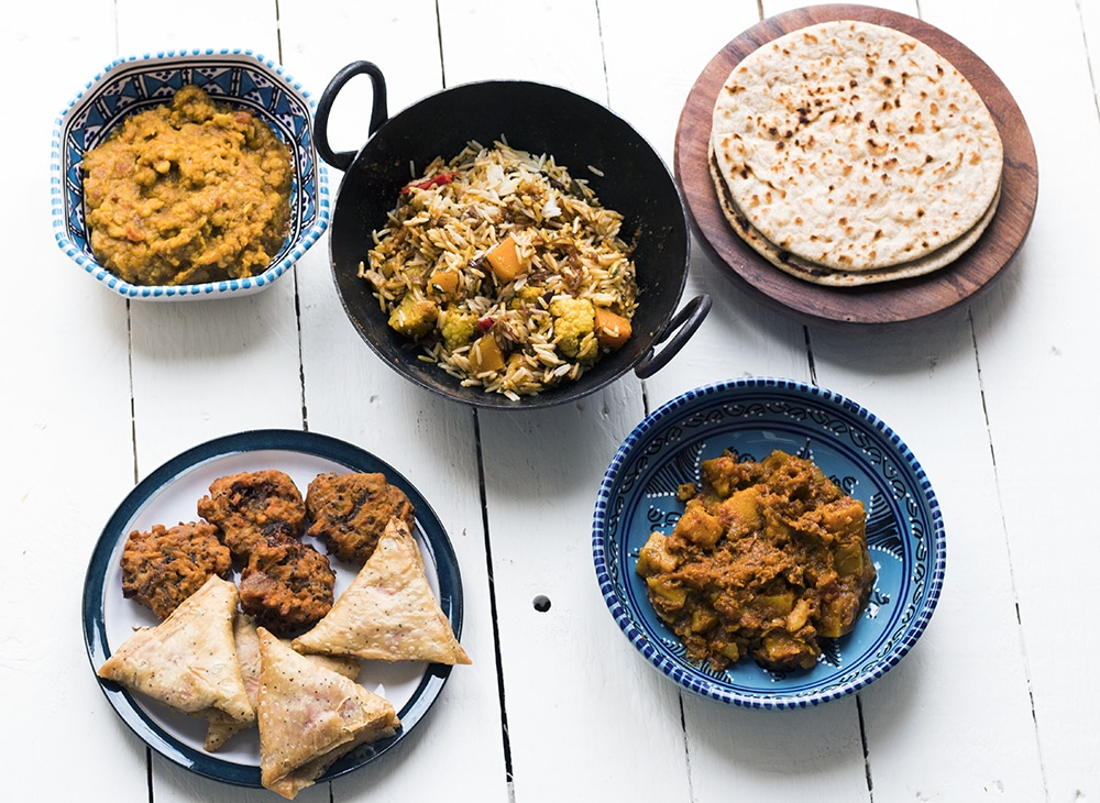 Clockwise from top left: tarka dahl, vegetable biryani, chapatis, bombay potatoes, beetroot and chilli samosas and sweet potato pakoras from the Sainsbury's Indian takeaway range.