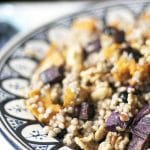 close up of Buckwheat salad in bowl with purple and orange sweet potatoes and blueberries