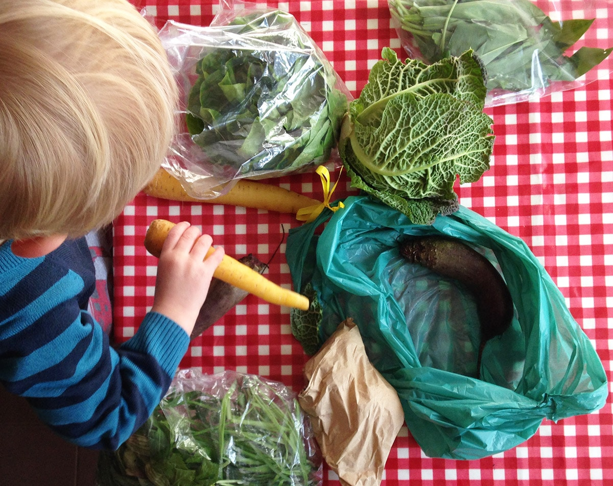 child unpacking vegetable bag
