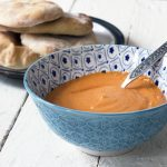 muhammara red pepper dip in bowl with flatbreads in background