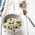 bowl of overnight oats with courgette, bowl of blueberries and jar of flaxseeds on white background