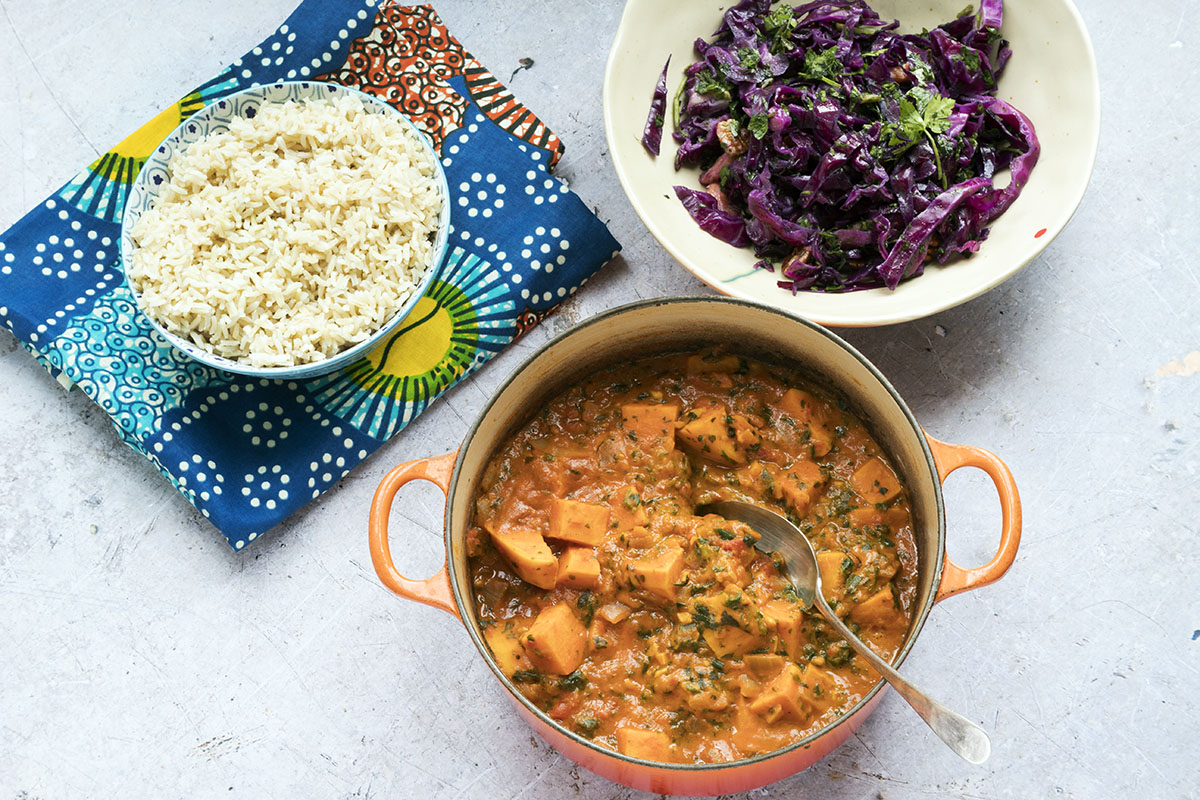 overhead show of African sweet potato peanut stew in orange pan with rice and cabbage salad