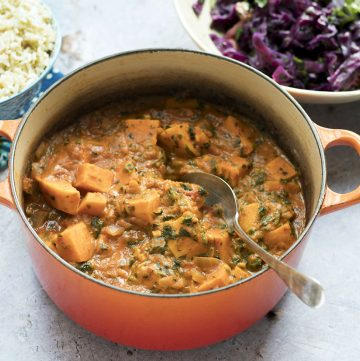 sweet potato peanut stew in orange pan with rice and cabbage salad in background