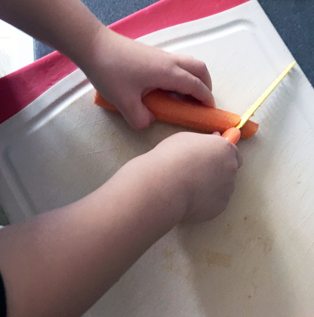 Little S, two, chopping carrots with a Foost kid-safe knife