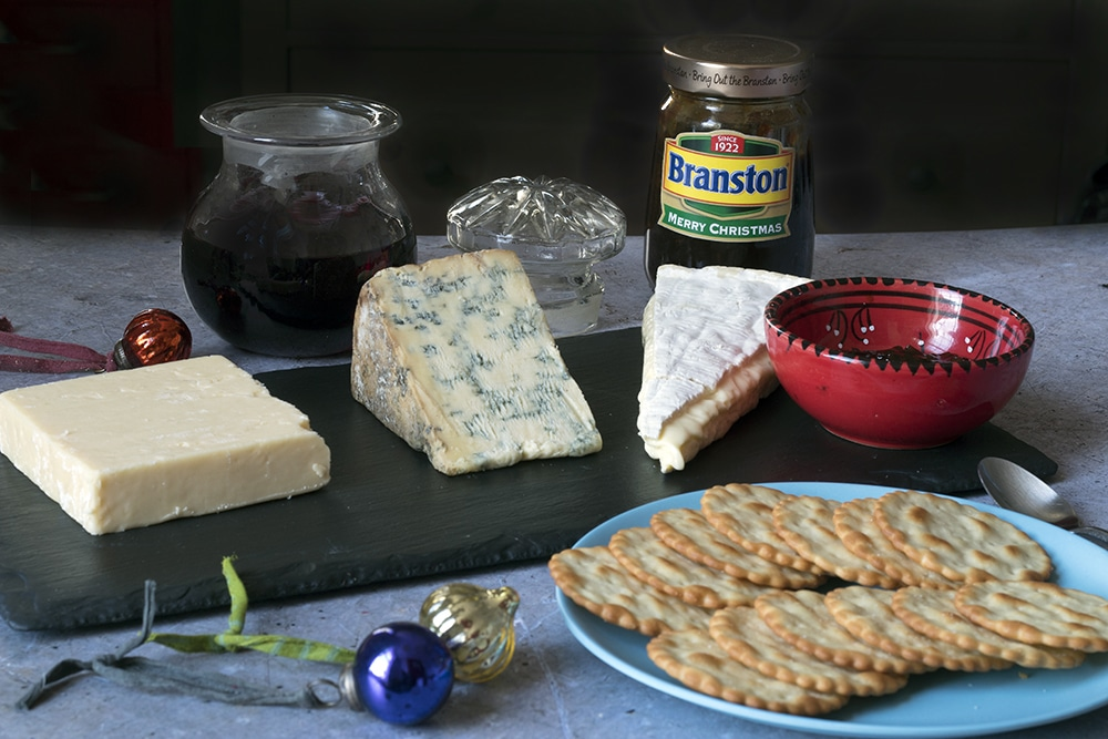 cheese and Branston pickle on board with red wine