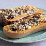 Vegan stuffed butternut squash with wild rice, cranberry and pecan