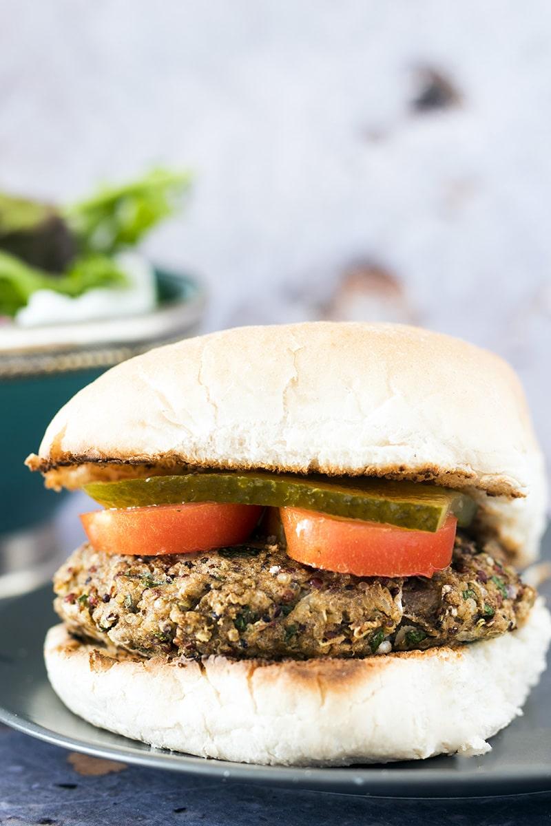 potato quinoa burger with gherkin and tomato in bun
