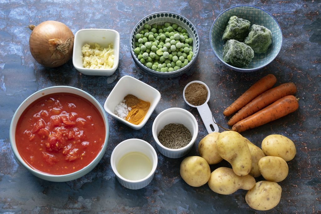 ingredients for Mixed vegetable curry on blue background